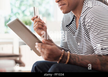 Mixed Race man shopping online with digital tablet