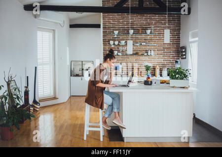 Caucasian woman using laptop in kitchen