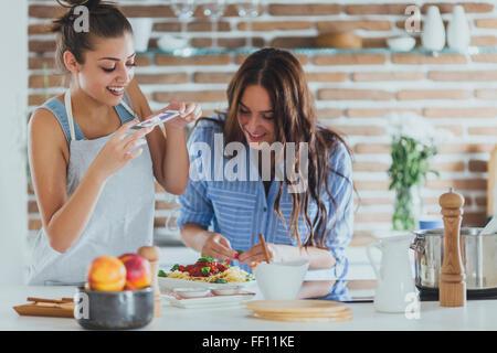 Les femmes de race blanche en photographiant les pâtes en cuisine Banque D'Images