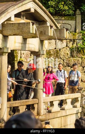 Les touristes à la base du temple Kiyomizu-dera pour attraper l'eau potable en utilisant des tasses avec la longue Banque D'Images