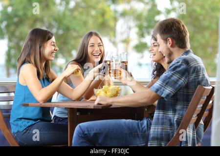 Groupe de 4 happy friends toasting dans un hôtel ou maison terrasse Banque D'Images