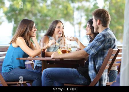Groupe de quatre amis parler et boire assis sur une terrasse à la maison Banque D'Images