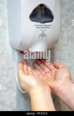 Distributeur de désinfectant pour les mains avec deux mains de race blanche. Le désinfectant pour les mains distributeur Banque D'Images
