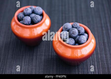 Des bleuets dans des pots d'argile sur bambou bleu foncé mat. Close up. Banque D'Images