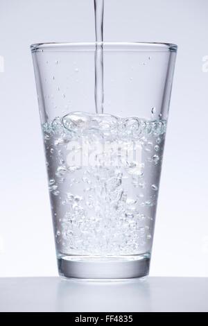L'eau courante ou le verre d'eau sur fond blanc Banque D'Images