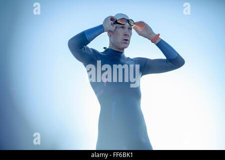 Un nageur dans une combinaison isothermique et la hat, son réglage de lunettes de natation. Banque D'Images