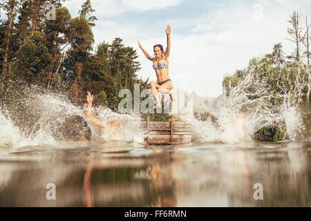 Portrait de jeunes femmes sauter dans un lac sauvage à partir de la jetée. Jeune fille sautant d'un quai au bord Banque D'Images