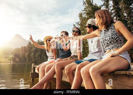 Portrait de jeunes amis assis sur un quai et le grillage de bières. Heureux les jeunes hommes et femmes ayant bières Banque D'Images