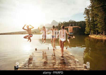 Vue arrière portrait de jeunes amis sauter dans un lac. Les jeunes en cours d'exécution et d'un saut d'une jetée Banque D'Images
