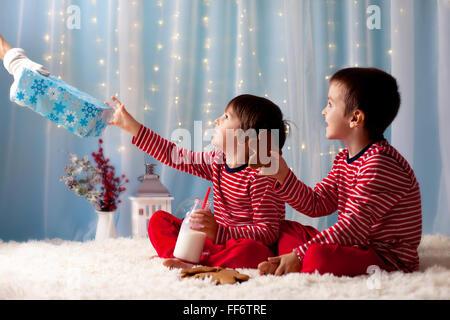 Deux petits garçons en pyjama, l'attente du Père Noël, Santa les présente, pour les enfants la préparation de lait Banque D'Images