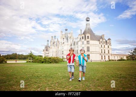 Deux adorables garçons de vêtements, la consommation de crème glacée assis sur une pelouse en face de la plus grand Banque D'Images