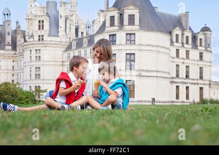 Deux adorables garçons et maman de vêtements, la consommation de crème glacée assis sur une pelouse en face de la Banque D'Images