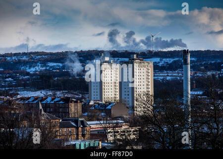 Deux blocs d'appartements, d'une cheminée et d'un tabagisme éolienne sur Glasgow South Side prises de Queens Park, Banque D'Images
