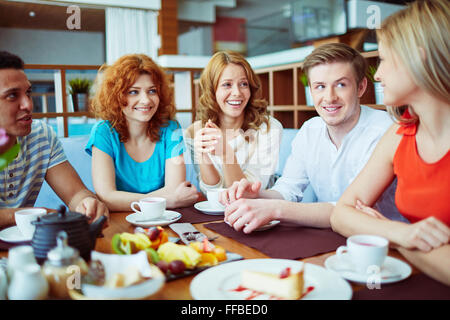Teenage friends talk while sitting in cafe Banque D'Images