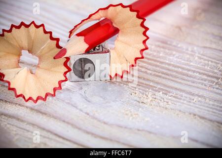 Taille-crayon avec et les copeaux sur fond de bois clair