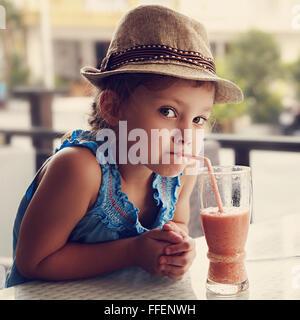 Relations sérieuses in cute kid curieux girl in hat boire le jus savoureux en été street cafe. Ton portrait gros Banque D'Images