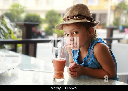 Relations sérieuses in cute kid curieux girl drinking jus savoureux en été street cafe Banque D'Images