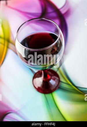 Résumé Contexte La conception de verres en verre de vin et de raisins sur fond multicolore. Banque D'Images