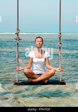 La jeune fille médite sur une balançoire dans la plage à Bali, Indonésie. Le point de droit. Banque D'Images