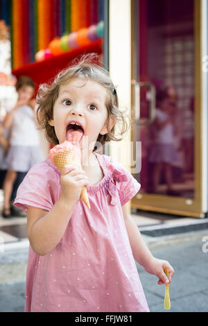 Little girl eating ice cream cone en plein air Banque D'Images