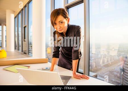 Femme architecte à office working on laptop Banque D'Images