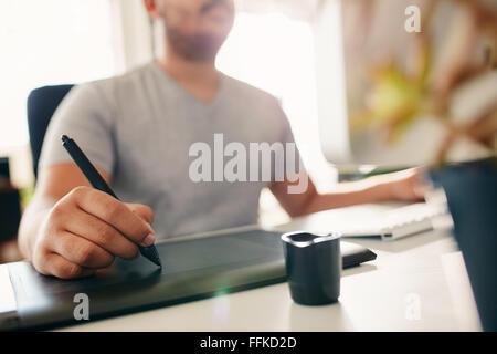 Main de l'homme designer travaillant à son bureau à l'aide du stylet tablette graphique et numérique. Banque D'Images