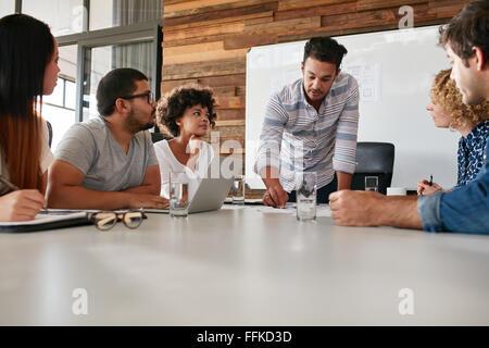 Les jeunes de l'équipe d'affaires à une réunion d'examen des progrès accomplis de l'entreprise. Les créatifs professionnels Banque D'Images