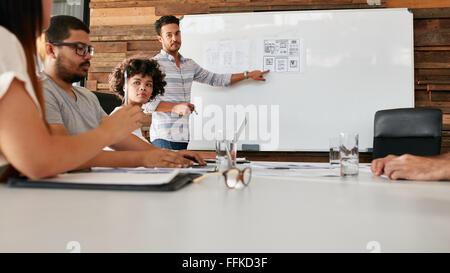 Young African woman sitting at conference table durant une présentation d'affaires. Équipe de professionnels de Banque D'Images