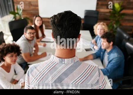 Vue arrière de l'homme portrait Présentation de l'entreprise donnant à ses collègues dans la salle de conférence. Les jeunes dans la salle de réunion.