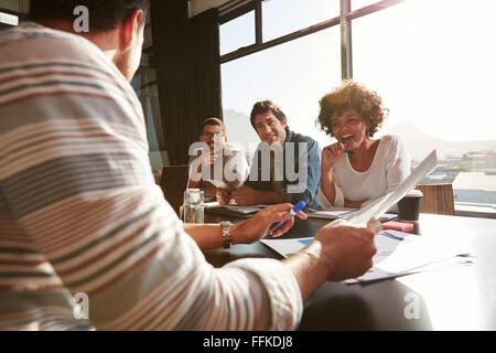 Shot de race mixte jeunes assis à une table pour discuter de nouvelles idées et créative. Smiling african woman Banque D'Images