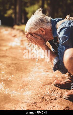 Side portrait of a senior man lave son visage dans le lac. Mature male hiker obtenir frais avec de l'eau du lac. Banque D'Images
