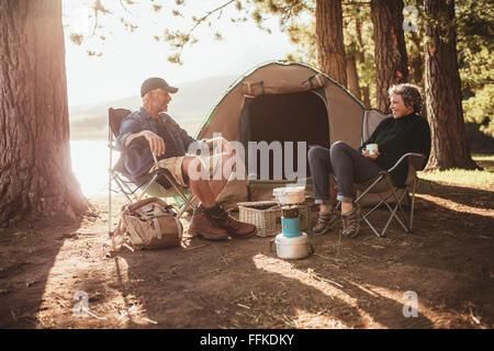 Portrait of happy senior couple sitting in chaises par tente au camping. Man and Woman relaxing et parler près d'un Banque D'Images