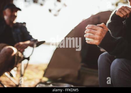 Portrait d'une main de femme tenant un café au camping avec un homme en arrière-plan, assis tous les deux à l'extérieur Banque D'Images