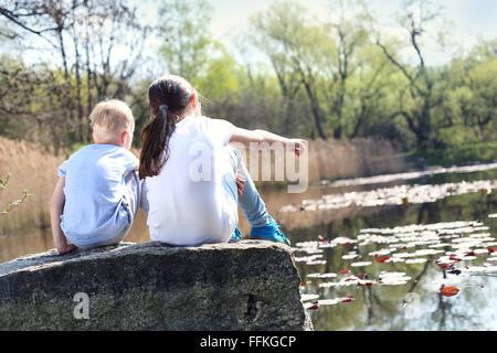 Le temps des vacances de détente au bord de l'eau. Deux enfants, la sœur aînée et son frère cadet assis sur la rive Banque D'Images