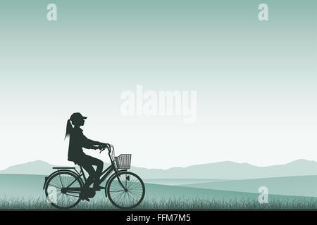 Une fille sur un vélo en silhouette avec paysage de prairie Banque D'Images