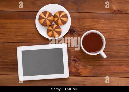 Tasse de thé et cookies une tablette numérique sur la table en bois. Vue d'en haut . Banque D'Images