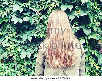 Vue arrière de Femme Debout contre les plantes de jardin Banque D'Images