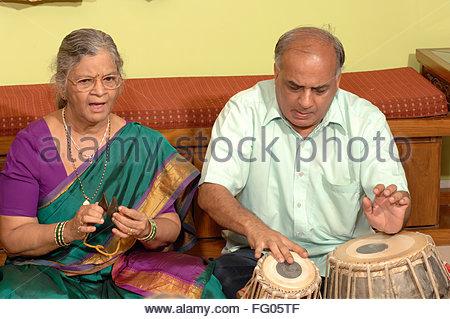 Indian Hindu vieille dame chanter les bhajans et l'homme jouant d'un instrument en chambre , Bombay Mumbai , Maharashtra Banque D'Images