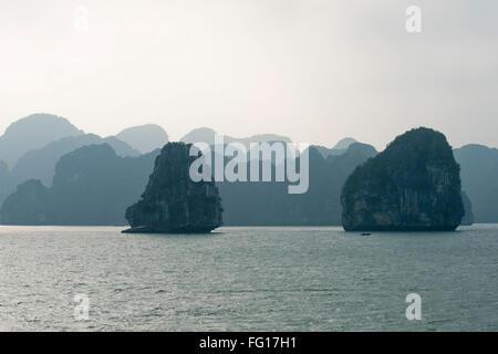 Misty image de calcaire de recul ou îles karstiques sortant de la mer dans la baie d'Halong, Vietnam du Nord, Banque D'Images
