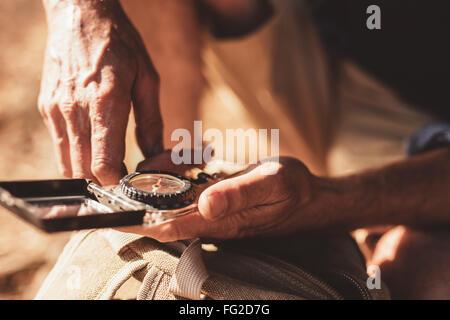 Close up portrait of man using compass pour les directions. L'accent sur boussole dans les mains d'un male hiker. Banque D'Images