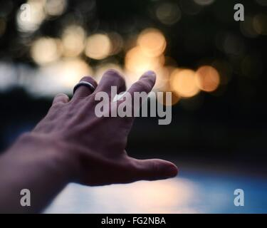 Portrait Of Cropped Hand Pointing at Defocused Lights