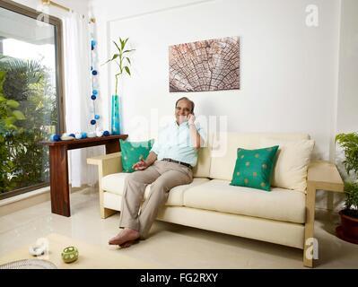 Old man talking on mobile sitting on sofa MR#702T Banque D'Images