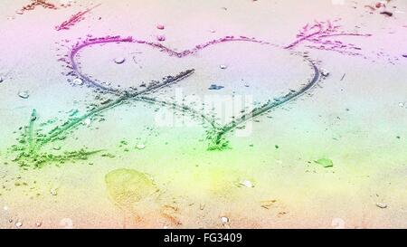 Coeur et flèche tracée dans le sable Banque D'Images