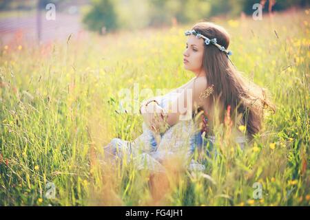 Young woman enjoying printemps météo à champ de fleur . Robe gitane hippie et Banque D'Images