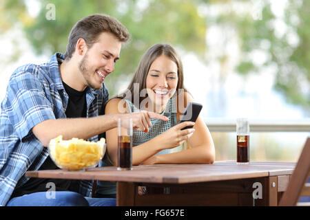 Le partage d'un couple assis sur un téléphone intelligent ou d'hôtel accueil terrasse Banque D'Images