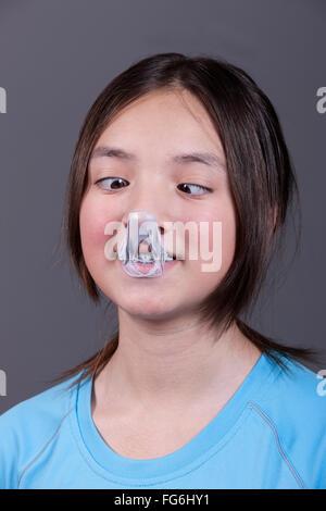 Une fille a un cross eyed regarder comme elle regarde les mess de la gomme sur son nez. Banque D'Images