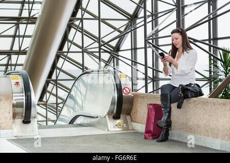 Business Woman texting on her smart phone après avoir pris une pause shopping au cours de sa journée de travail; Banque D'Images