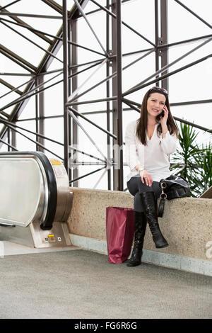 Business Woman talking sur son téléphone portable après avoir pris une pause shopping au cours de sa journée de Banque D'Images