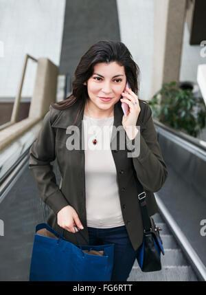 Young business woman talking sur son téléphone portable après avoir pris une pause shopping au cours de sa journée Banque D'Images