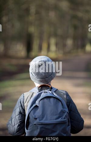 Un garçon avec un sac à dos randonnée dans les bois Banque D'Images